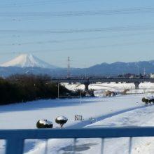 雪の河川敷の先に真っ白い富士山